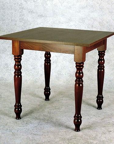tavolo in legno quadrato con gambe tonde e lavorate a